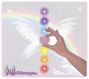 Hand holding Rose Quartz heart and the seven chakras